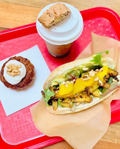 Vegan Chicken Curry (hier nog op een Corn Bun) van het kioskmenu samen met een vegan carrot cake en een cappuccino.